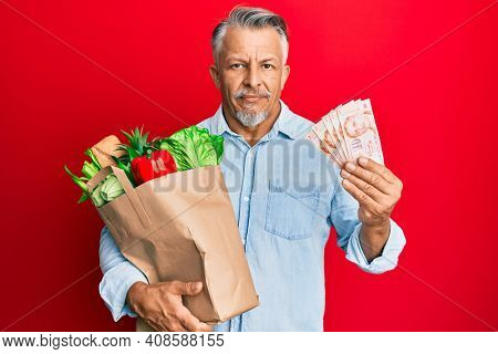 Middle age grey-haired man holding groceries and singapore dollars banknotes relaxed with serious expression on face. simple and natural looking at the camera.