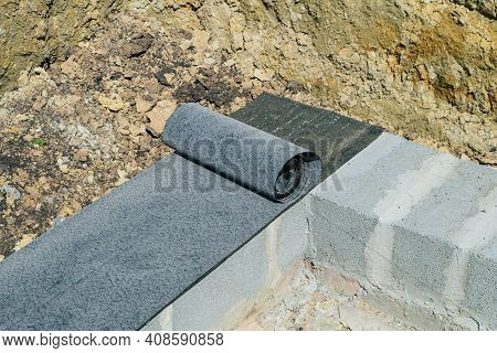 Bituminous Waterproofing Roll Material Is Laid On Wall Of Concrete Blocks