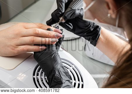Hardware Manicure Process In A Beauty Salon. Close-up Of Manicurist's Hands In Black Gloves Using Au