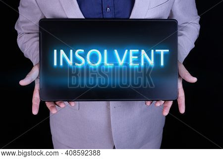 Insolvent Word, Text Written In Neon Letters On A Laptop Which Is Being Held By A Businessman In A G