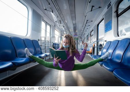 Very Flexible Wearing Mask Woman Reading Book In The Subway Car Sitting In The Gymnastic Split. Conc