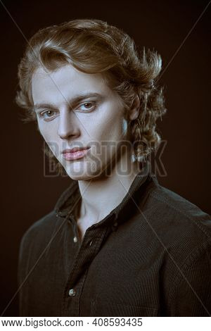 Portrait of a pale handsome young man with wavy blond hair in dark shirt looking at the camera. Black background with copy space. Men's beauty.