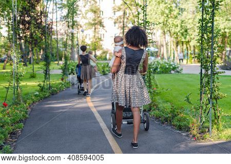 Two Young Mothers Pushing Strollers In Summer Park. Women In The Park Walking With Strollers