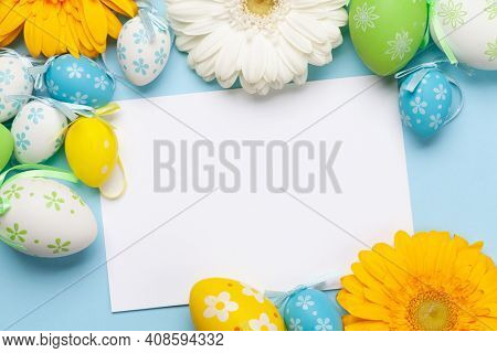 Easter greeting card with gerbera flowers and colorful easter eggs. Top view flat lay with space for your greetings