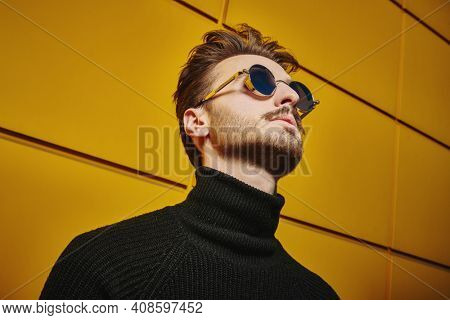 Portrait of a stylish young man in black pullover and round mirror sunglasses looking up on a street by the yellow industrial wall. Male fashion. Urban style.