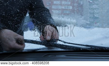 A Look Through The Windshield Of A Car At The Hands Of A Driver Who Removes Snow From The Car Wipers