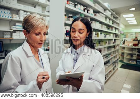 Happy Young Female Pharmacist Discussing Work With Senior Colleague Using Digital Tablet In Chemist