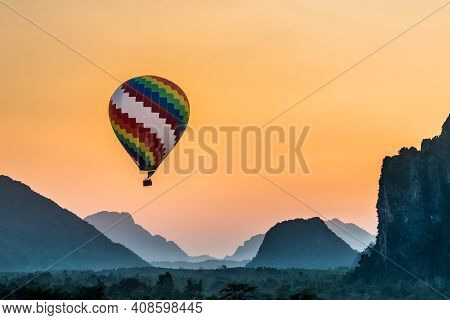 Colorful Hot Air Ball Floats Through The Misty Morning Mountain Range Of Vang Viang In Loas Asia