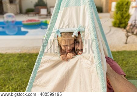 Father Playing Hide And Seek With His Little Daughter While Camping In The Backyard By The Swimming