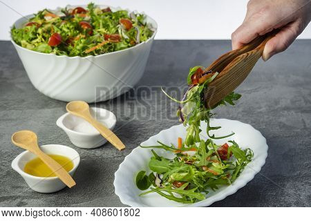 Woman's Hand Serving Salad Of Lettuce, Tomatoes, Rugula, Various Green Vegetables With Wooden Tongs