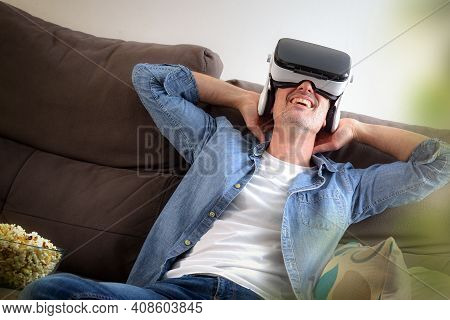 Relaxed Entertaining Man At Home Watching Movies In Virtual Reality Glasses Sitting On The Couch Wit