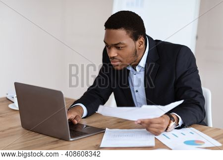 African American Manager With Documents Checking Marketing Report, Using Laptop In Office, Copy Spac