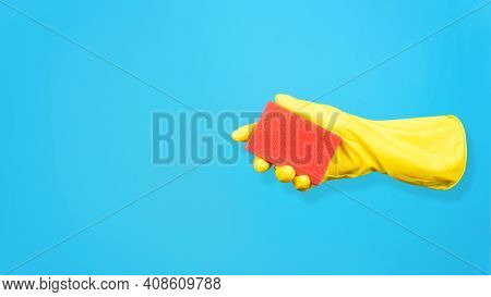 Levitating Yellow Glove Holding Cleaning Sponge On Blue Background. Creative Concept Of Washing And
