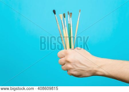 Male Hand Holding Collection Paint Brushes On Blue Background, Copy Space. Tools For Creativity, Fin