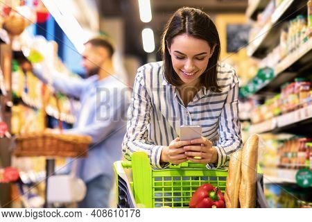 Smiling Female Customer Doing Grocery Shopping Using Smartphone Walking With Cart In Supermarket. Se