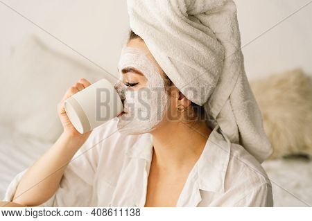 Beautiful Woman Applying Facial Mask And Drinking Tea In Bed