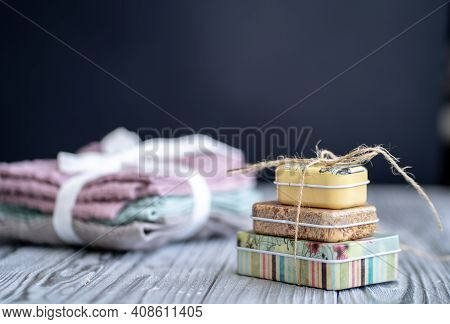 By Raging Rewinded Tin Boxes With Scented Soap. In The Background Is A Stack Of Small Towels Rewinde