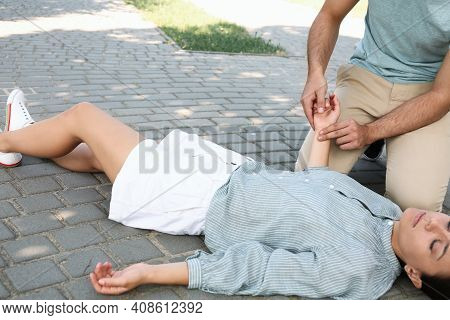 Young Man Checking Pulse Of Unconscious Woman Outdoors. First Aid