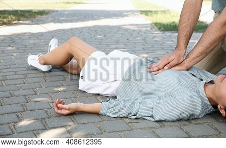 Young Man Performing Cpr On Unconscious Woman Outdoors, Closeup. First Aid