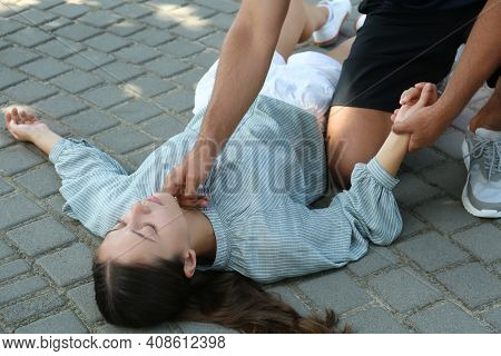 Man Checking Pulse Of Unconscious Young Woman Outdoors. First Aid