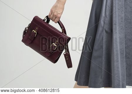 Small Red Leather Bag In A Womans Hand On A White Background. Shoulder Handbag. Woman In A White Shi