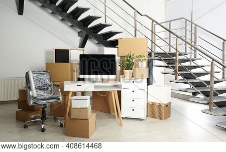 Cardboard Boxes And Furniture Near Stairs In Office. Moving Day