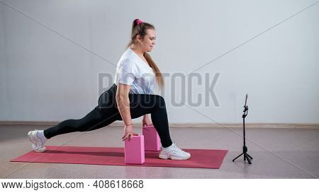 Young Fat Caucasian Woman Lunges On A Sports Mat. Charming Plus Size Girl In Sportswear Is Doing Fit