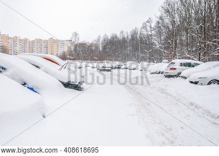 Snow-covered Street Road And Cars Under The Snow. Heavy Snowstorm, Blizzard Traffic. Climate Weather