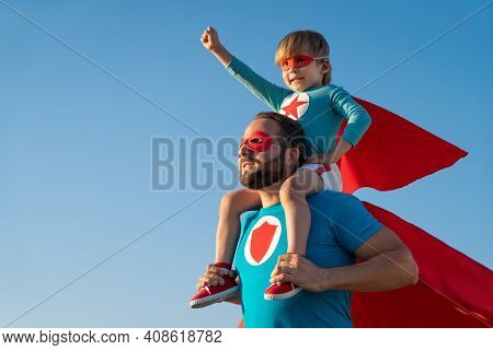 Family Of Superheroes Having Fun Outdoor. Father And Son Playing Against Blue Summer Sky Background.