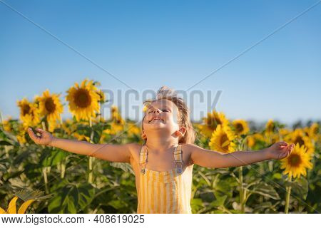 Happy Child Playing Outdoor In Spring Field