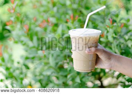 Close Up Hand Holding Glass Of Ice Coffee With Green Leaves Nature Background, Selective Focus
