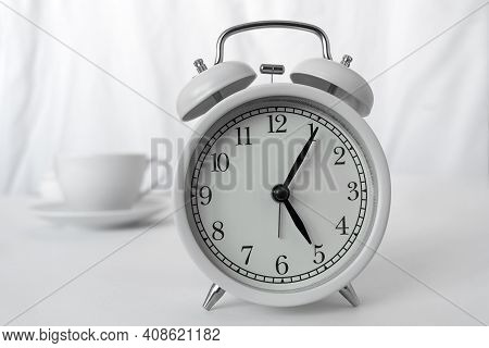 The White Alarm Clock Is On The Table.behind It Is A White Cup Of Coffee On A Light Background. The