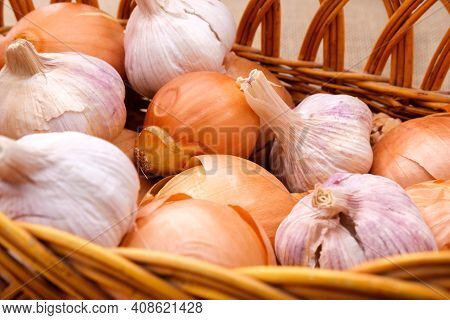 Garlic And Onion Bulbs Are In A Wicker Basket.