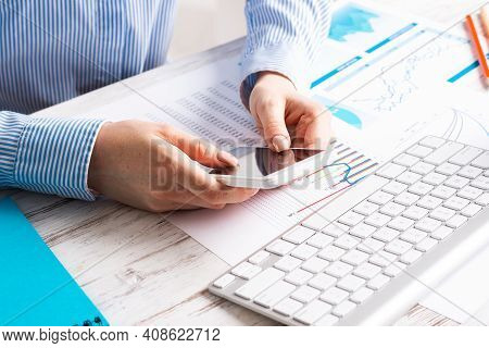 Business Lady Sitting At Desk And Using Smartphone. Corporate Office Workplace With Computer Keyboar