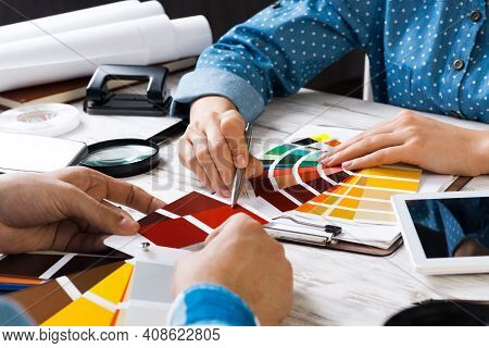 Cropped Image Of Designer And Client Meeting In Office. Creative Workspace With Color Swatches And T