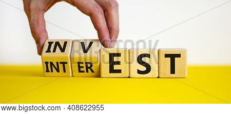 Invest Or Interest Symbol. Businessman Turns Wooden Cubes And Changes The Word 'invest' To 'interest