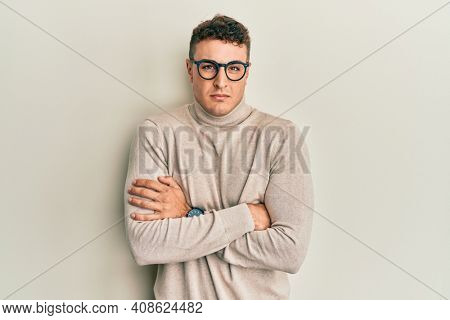 Hispanic young man wearing casual turtleneck sweater shaking and freezing for winter cold with sad and shock expression on face