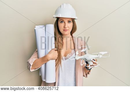 Young blonde woman wearing safety helmet holding blueprints and drone relaxed with serious expression on face. simple and natural looking at the camera.