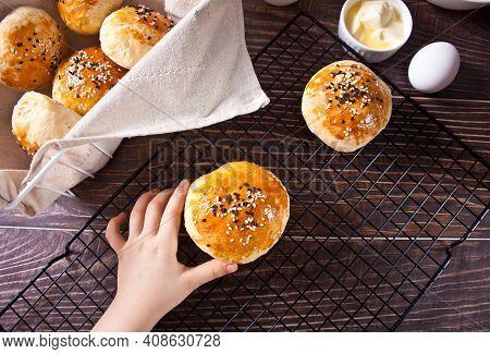 Fresh Homemade Whole Grain Burger Buns With Sesame. Kid Hand Take A One Bun