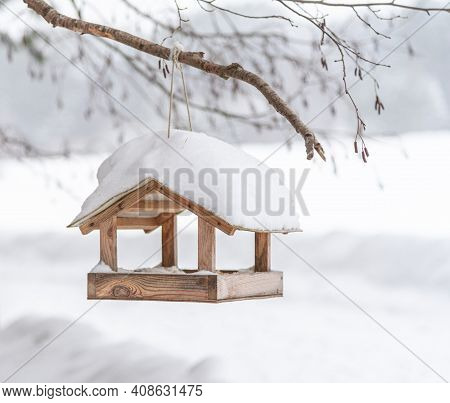 Empty Bird Feeder On The Background Of A Winter Landscape. Feeding Birds In Winter. A Small Wooden F