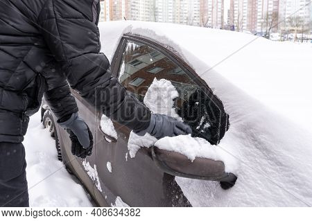 A Man Clears Snow From His Car Window. Car In The Snow After A Night Blizzard