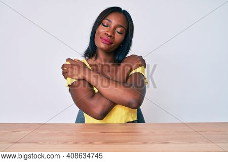 Young african american woman wearing casual clothes sitting on the table hugging oneself happy and positive, smiling confident. self love and self care