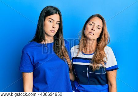 Hispanic family of mother and daughter wearing casual clothes over blue background looking sleepy and tired, exhausted for fatigue and hangover, lazy eyes in the morning.