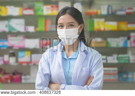 Portrait Of Asian Woman Pharmacist Wearing A Surgical Mask In A Modern Pharmacy Drugstore, Covid-19