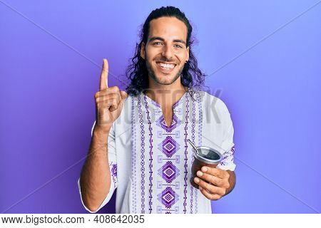 Young handsome man with long hair drinking mate infusion smiling with an idea or question pointing finger with happy face, number one