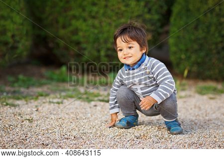 Portrait Of A Little Eastern Hadsome Baby Boy Playing With Pebbles Outdoor In The Park. Arabian Chil