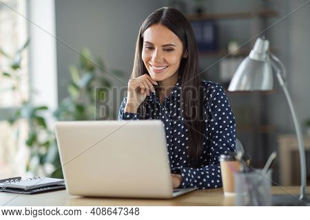 Photo Of Beautiful Minded Lady Look Laptop Hold Hand Chin Sit Table Secretary Work In Office Indoors