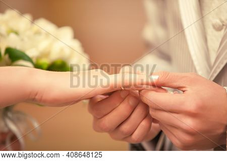 Close-up Of The Groom's Hands Putting The Wedding Ring On The Bride's Hand Indoors.