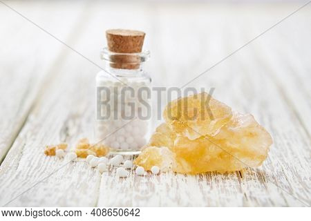 Sulphur crystal with homeopathic globules on white wooden background