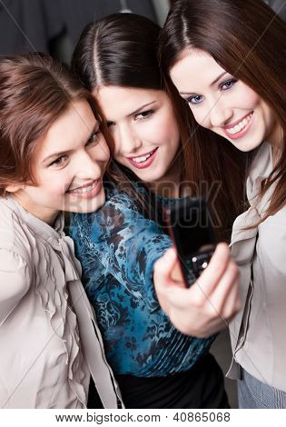 Three beautiful women with ling dark hair snap themselves after shopping